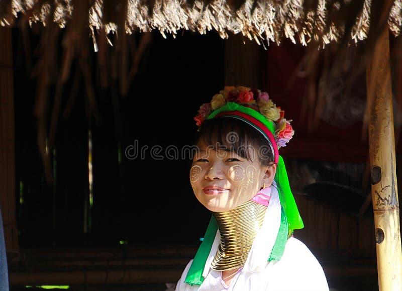 BY FÖR LONGNECK KAREN, THAILAND - DECEMBER 17 2017: Lång halskvinna som framme sitter av en koja royaltyfri foto
