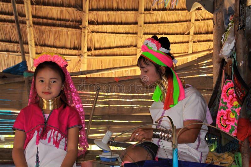 BY FÖR LONGNECK KAREN, THAILAND - DECEMBER 17 2017: Två flickor från den långa halsstammen som spelar i kojan royaltyfri fotografi