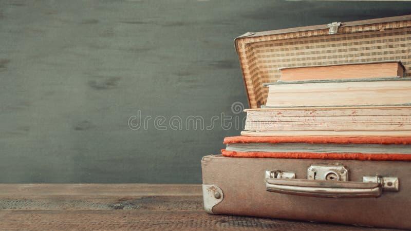 För loppläder för tappning gamla klassiska resväskor med bunten av gamla böcker och album royaltyfria foton
