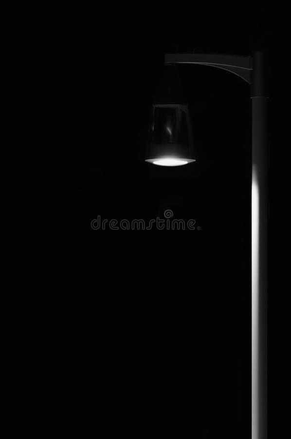 För lyktalampan för den ljusa liten deserterade den utomhus- Pole stolpen, metaforen för ensamhetbegreppsensamhet, upplyst fönste royaltyfria bilder