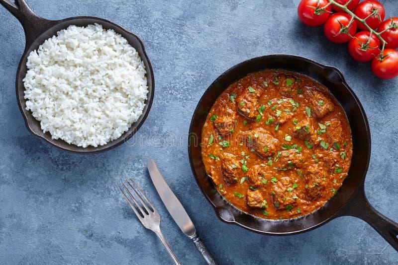 För Madras för traditionellt nötkött mat indisk kryddig lamm med ris och tomater i gjutjärnpanna royaltyfria bilder