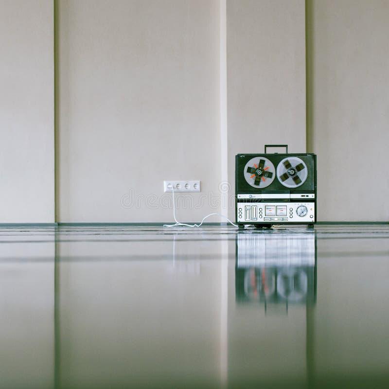 För magnetbandspelare för tappning parallellt anseende på golvet nära väggen royaltyfria bilder