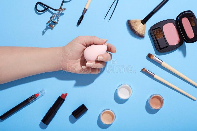 För makeup och hållande makeupsvamp för kvinnlig hand på blå bakgrund royaltyfri bild