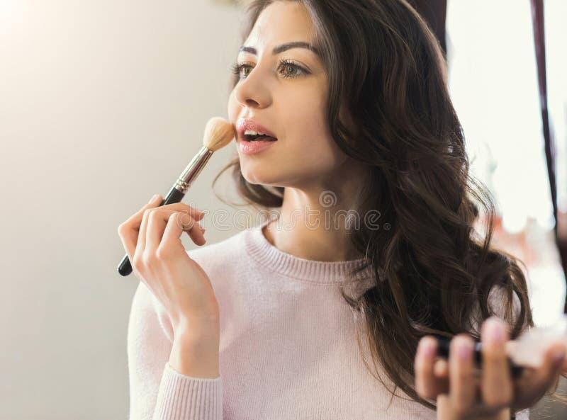 För makeuppulver för ung kvinna fundament i salong arkivbild