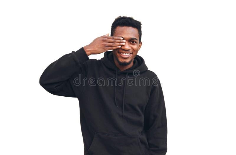 För manbokslut för stående lycklig le afrikansk framsida med handen och se av ett öga som bär den svarta hoodien som isoleras på  arkivfoton