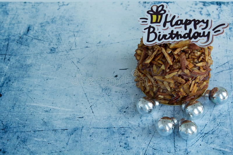 För mandelchoklad för lycklig födelsedag kaka på blå pastellfärgad bakgrund arkivbild