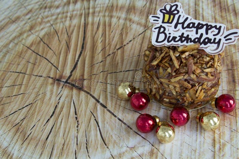 För mandelchoklad för lycklig födelsedag kaka på Wood bakgrund royaltyfri foto
