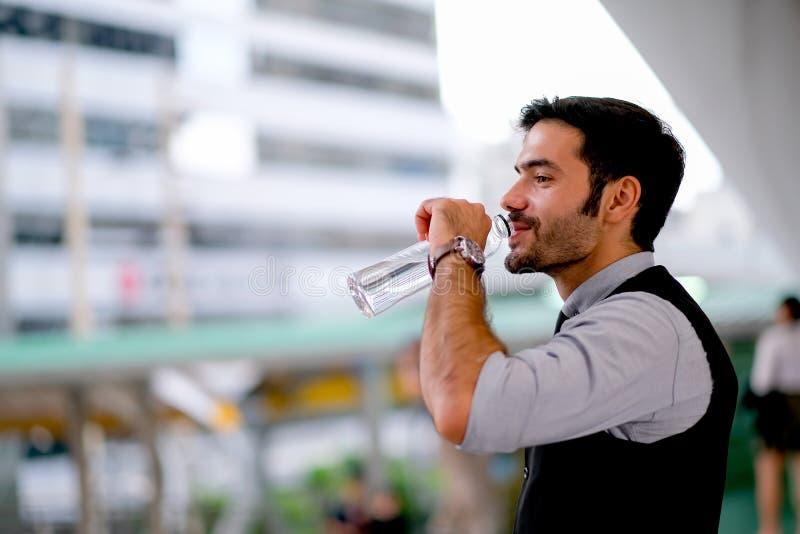 För mandrink för vit affär stiligt vatten från flaskan under dagtid i staden för uppfriskning royaltyfri bild