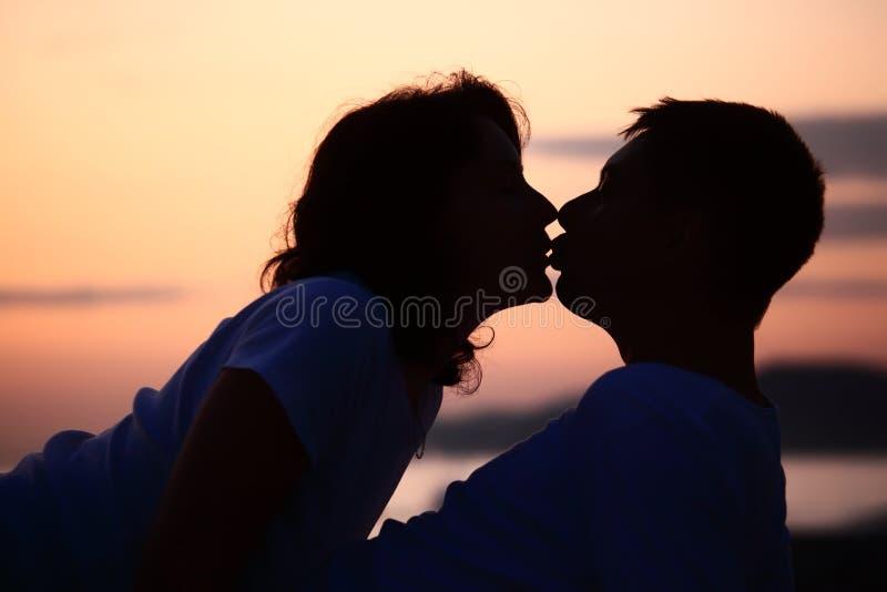 för mansilhouette för strand kyssande kvinna royaltyfria bilder