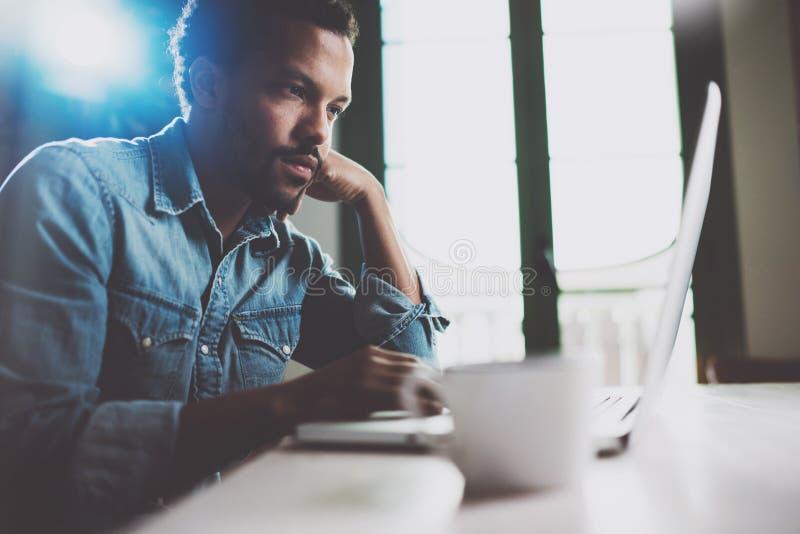 För marknadsföringsnyheterna för eftertänksam ung afrikansk man läs- bärbar dator, medan sitta på tabellen på en solig morgon Beg arkivbilder