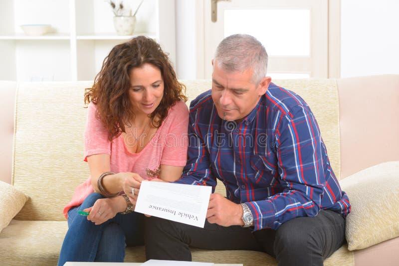 För medelförsäkring för par undertecknande avtal arkivfoto