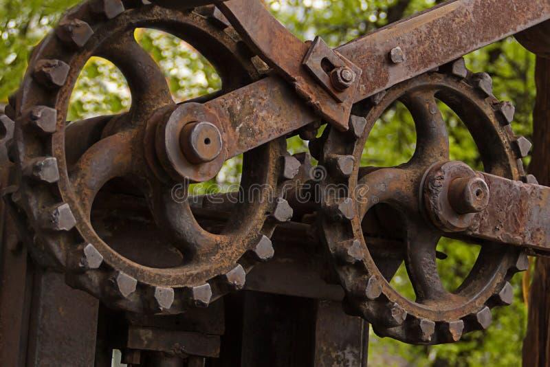 För mekanismmotor för stort kugghjul gammal grupp av närbild för industriell för grunge för axelbakgrund rostig för gata för sågv arkivbild
