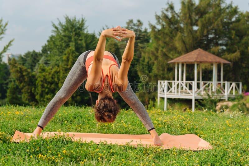 För mindfulnessmeditation för kvinna praktiserande anseende på gräs fotografering för bildbyråer