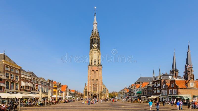 För mittmarknad för delftfajans nederländsk historisk fyrkant med folk som sitter på terrasser som tycker om det härliga vädret royaltyfria foton