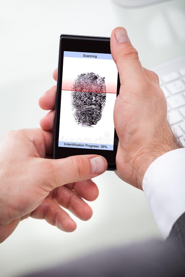 För mobiltelefonscanning för affärsman hållande finger royaltyfri fotografi