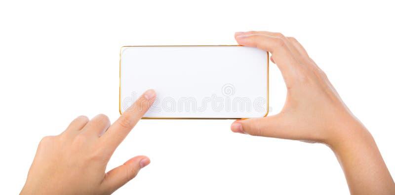 För mobiltelefonsmartphone för kvinnlig hand hållande guld- åtlöje upp royaltyfria foton