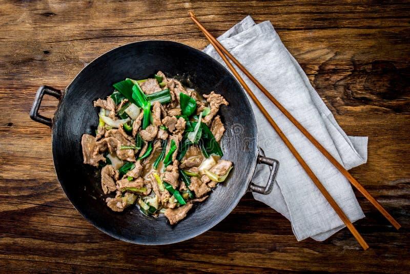 För mongoliannötkött för traditionell kines småfisk för uppståndelse i kinesiskt gjutjärn wokar med matlagningpinnar, träbakgrund arkivbild