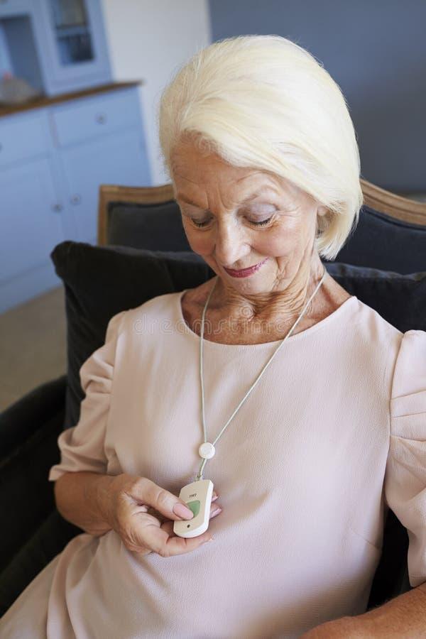 För nödlägelarm för hög kvinna hemmastadd användande knapp för appell royaltyfri foto