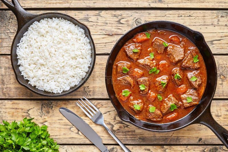 För nötköttkött för gulasch som tjänade som hemlagad ungersk mat för soppa för ragu lagades mat med kryddig skysås i gjutjärnpann royaltyfria foton