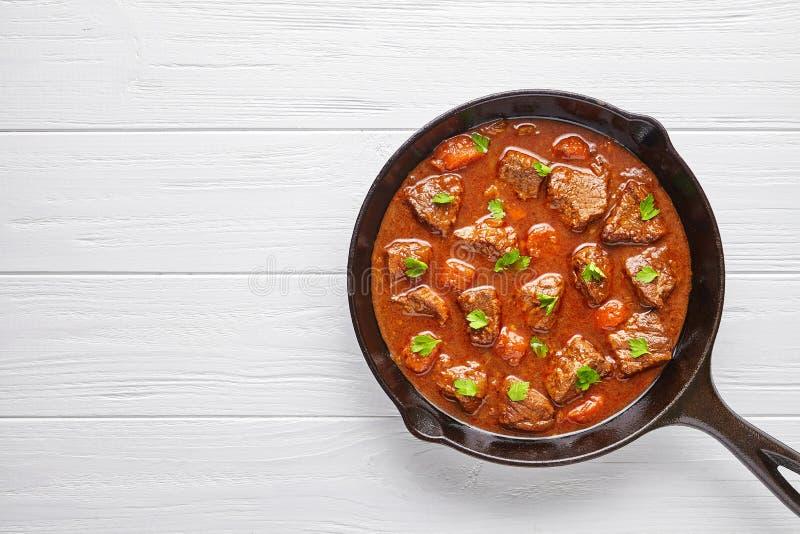 För nötköttkött för gulasch traditionell hemlagad ungersk mat för soppa för ragu med kryddig sky i gjutjärnpannakastrull royaltyfria bilder