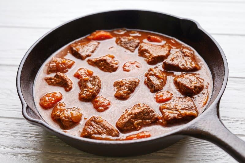 För nötköttkött för gulasch traditionell ungersk mat för soppa för ragu med kryddig sky i gjutjärnpanna royaltyfri foto