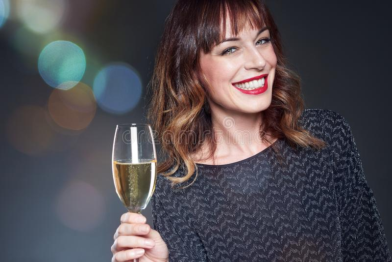 För nattparti för kvinna bärande klänning med ett exponeringsglas av champagne på mörk bakgrund Dam med långt fira för lockigt hå royaltyfri foto