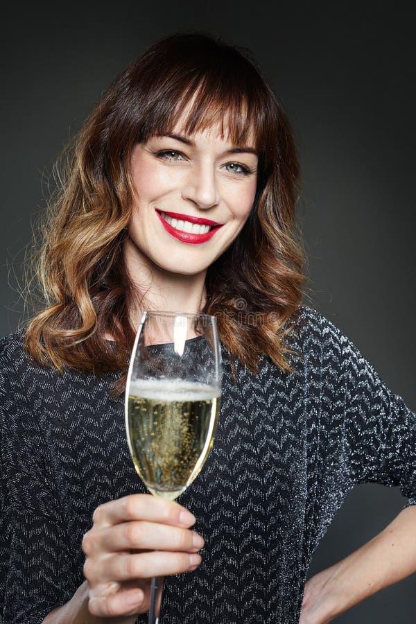 För nattparti för kvinna bärande klänning med ett exponeringsglas av champagne på mörk bakgrund Dam med långt fira för lockigt hå royaltyfri bild