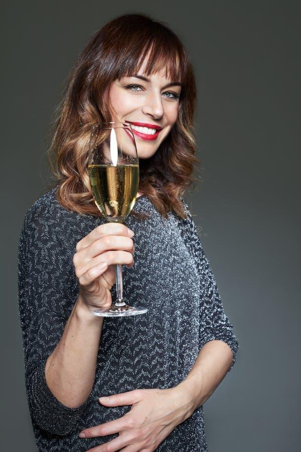 För nattparti för kvinna bärande klänning med ett exponeringsglas av champagne på mörk bakgrund Dam med långt fira för tänder för royaltyfria foton