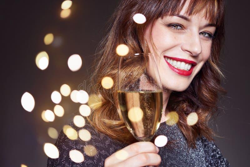 För nattparti för kvinna bärande klänning med ett exponeringsglas av champagne på mörk bakgrund Dam med långt lockigt hår och per royaltyfri fotografi