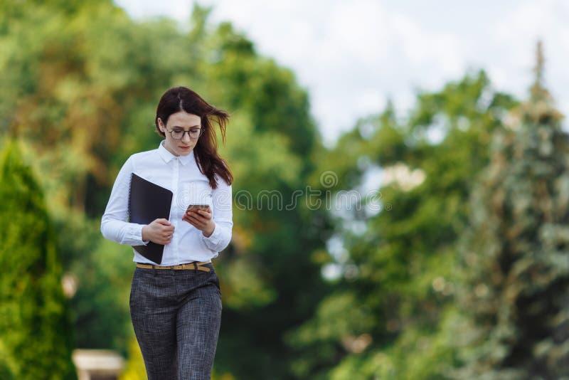 För ofbusinesskvinna för främre sikt som bärande vit skjorta går och använder en smart telefon på en stadsgata arkivbilder