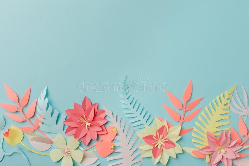 För origamifower för pappers- hantverk idé för garnering idérik tropiska blommor och sidor på blå pastellfärgad bakgrund, sommart arkivfoto