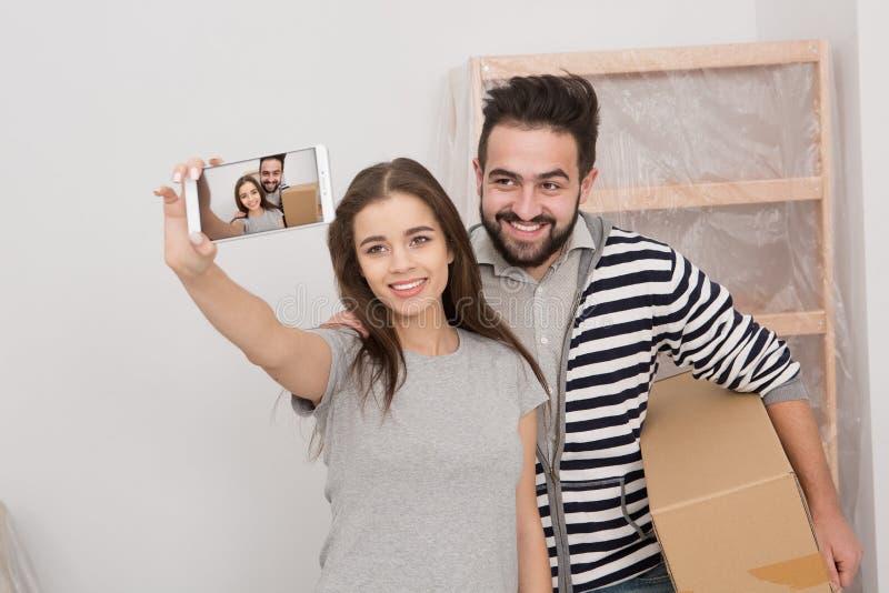 För pardanande för förflyttning sköt ung lycklig selfie i deras nya lägenhet arkivbild