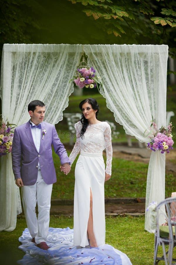 För parinnehav för nygift person lyckliga händer på gången för bröllopceremoni fotografering för bildbyråer