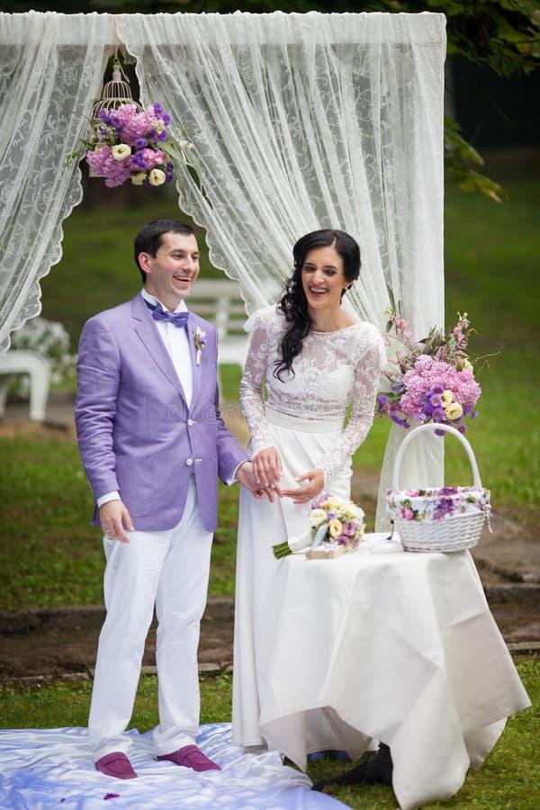 För parinnehav för nygift person lyckliga händer på gången för bröllopceremoni arkivbild