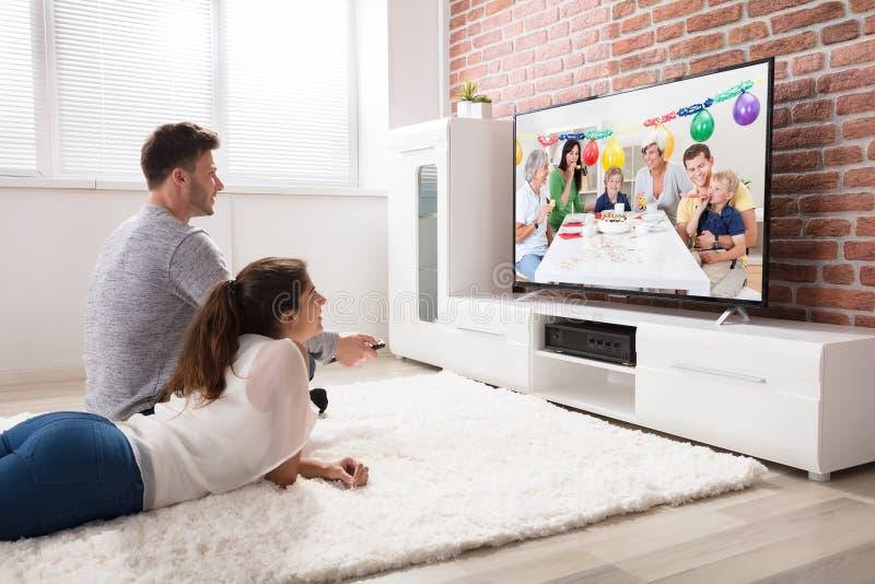 För partiberöm för par hållande ögonen på video på television arkivbild