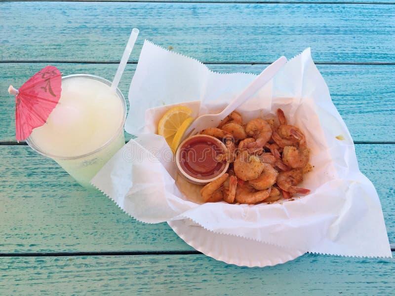 ` För Peel N äter kokt räka med cajunsmaktillsats och en trevlig kall fryst lemonad för att dricka arkivfoton