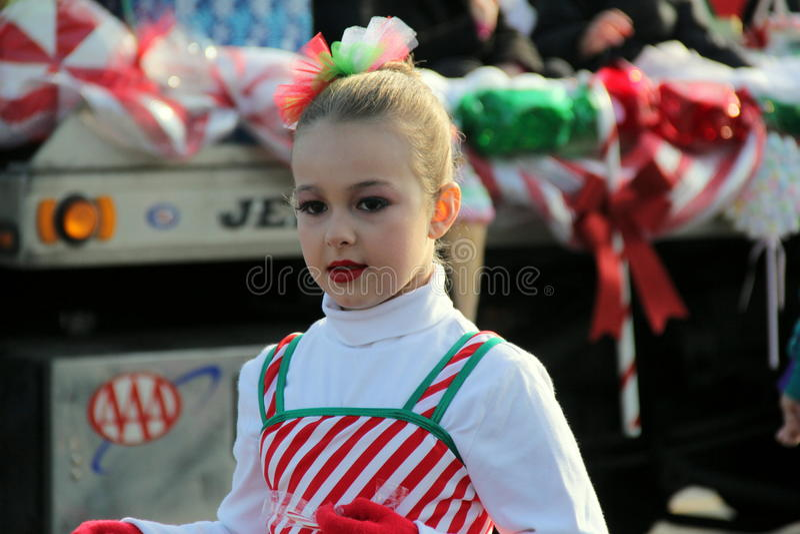För pepparmintpinnen för unga flickan som ståtar den iklädda dräkten marscherar i ferie, Glens Falls, New York 2014 arkivbild