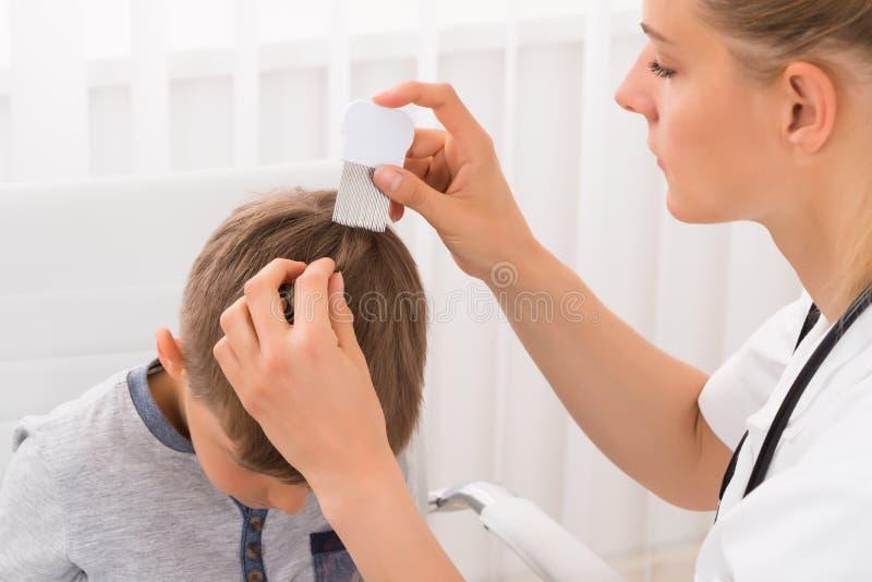 För pojke` s för doktor Doing Treatment On hår royaltyfria bilder