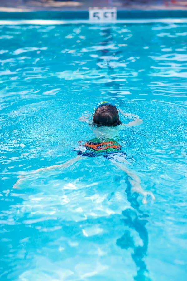 För pojkedanande för liten unge konkurrens för simning i pöl arkivfoton