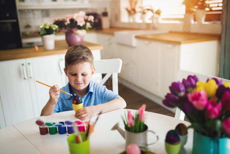 För pojkefärgläggning för den lilla ungen ägg för påsk semestrar i inhemskt kök royaltyfria bilder