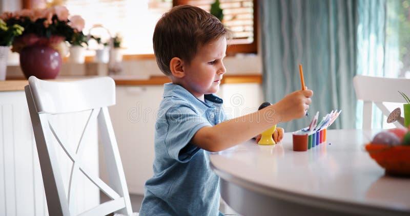 För pojkefärgläggning för den lilla ungen ägg för påsk semestrar i inhemskt kök royaltyfri foto