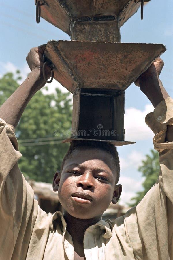 För pojkesegdragning för stående ghananska ugnar på huvudet arkivbilder