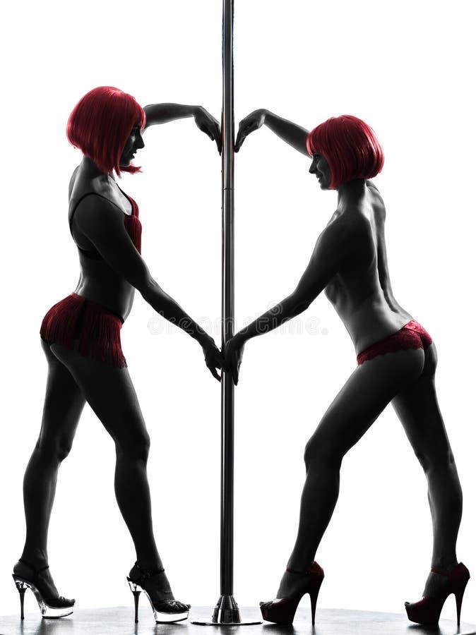 För poldansare för två kvinnor silhouette arkivbild