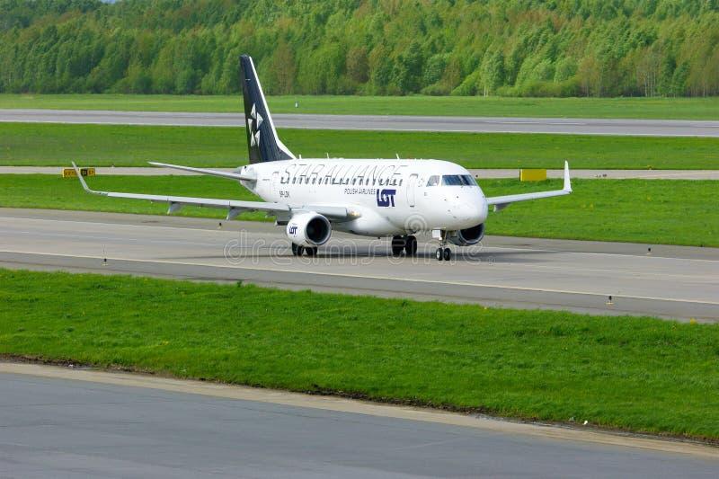 För polermedelflygbolag för LOTT (Star Alliance livré) Embraer ERJ-170 flygplan i Pulkovo den internationella flygplatsen i St Pe royaltyfri bild