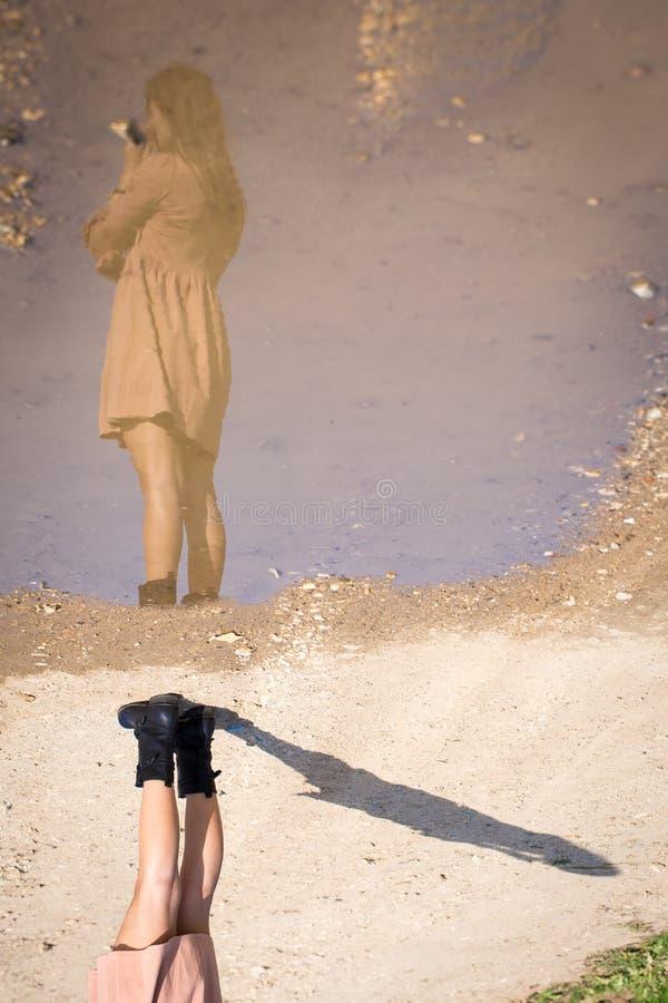 För reflexionspöl för ung kvinna som modell poserar inverterat uppochnervänt arkivfoto