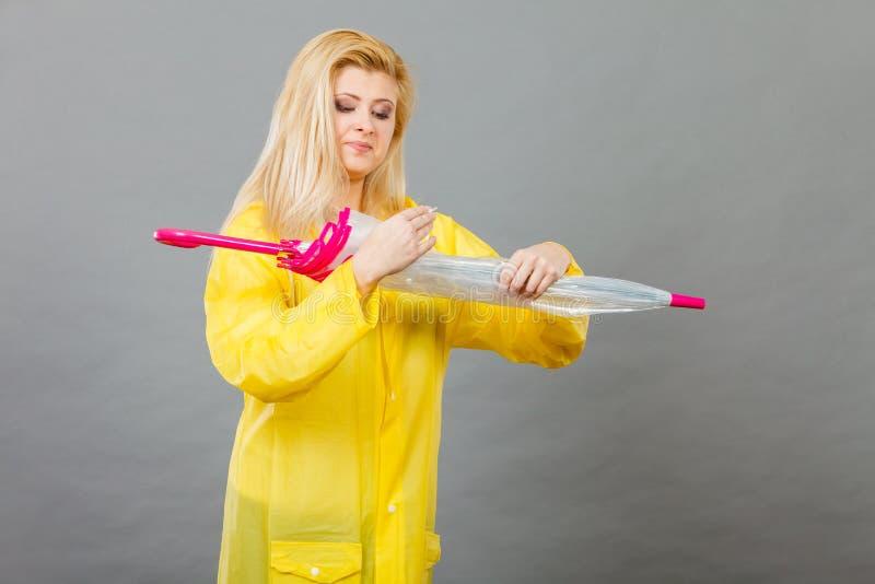 För regnrockbokslut för kvinna bärande paraply fotografering för bildbyråer