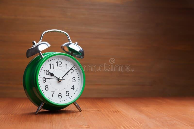 För ringklockamorgon för klassiker grön tid för vak-upp på wood backgroun royaltyfria bilder