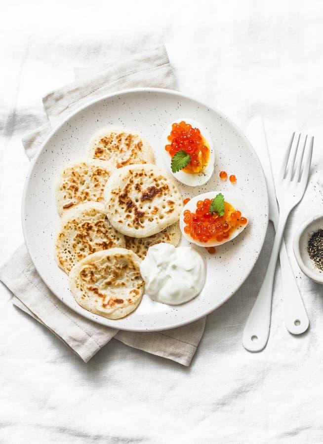 För rismjöl för gluten fria pannkakor och kokta ägg med den röda kaviaren - läcker frukost, frunch på en ljus bakgrund arkivfoton
