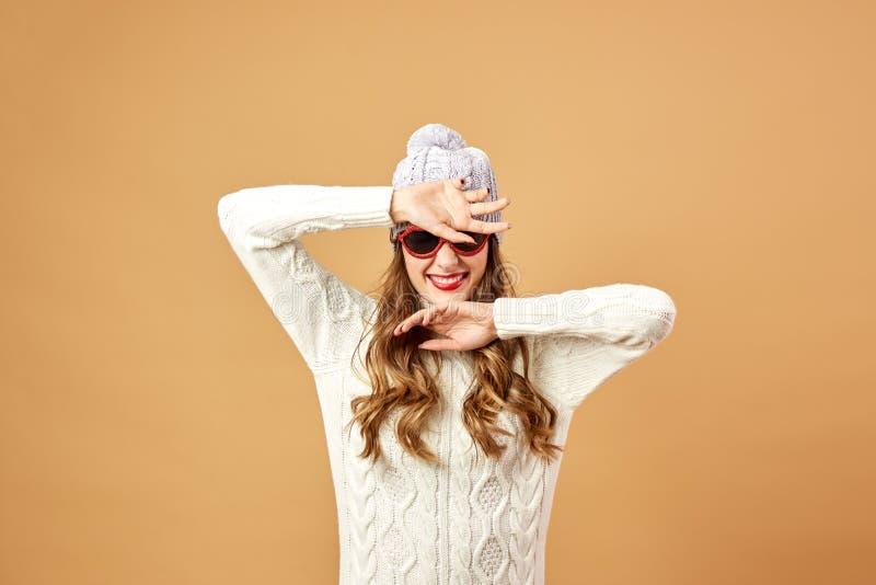 För rolig flicka som de rika för iklädd vit stucken tröja och hatt- och solglasögonär rolig på en beige bakgrund i studion royaltyfria bilder