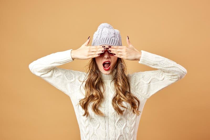 För rolig flicka som de rika för iklädd vit stucken tröja och hatt- och solglasögonär rolig på en beige bakgrund i studion arkivfoton
